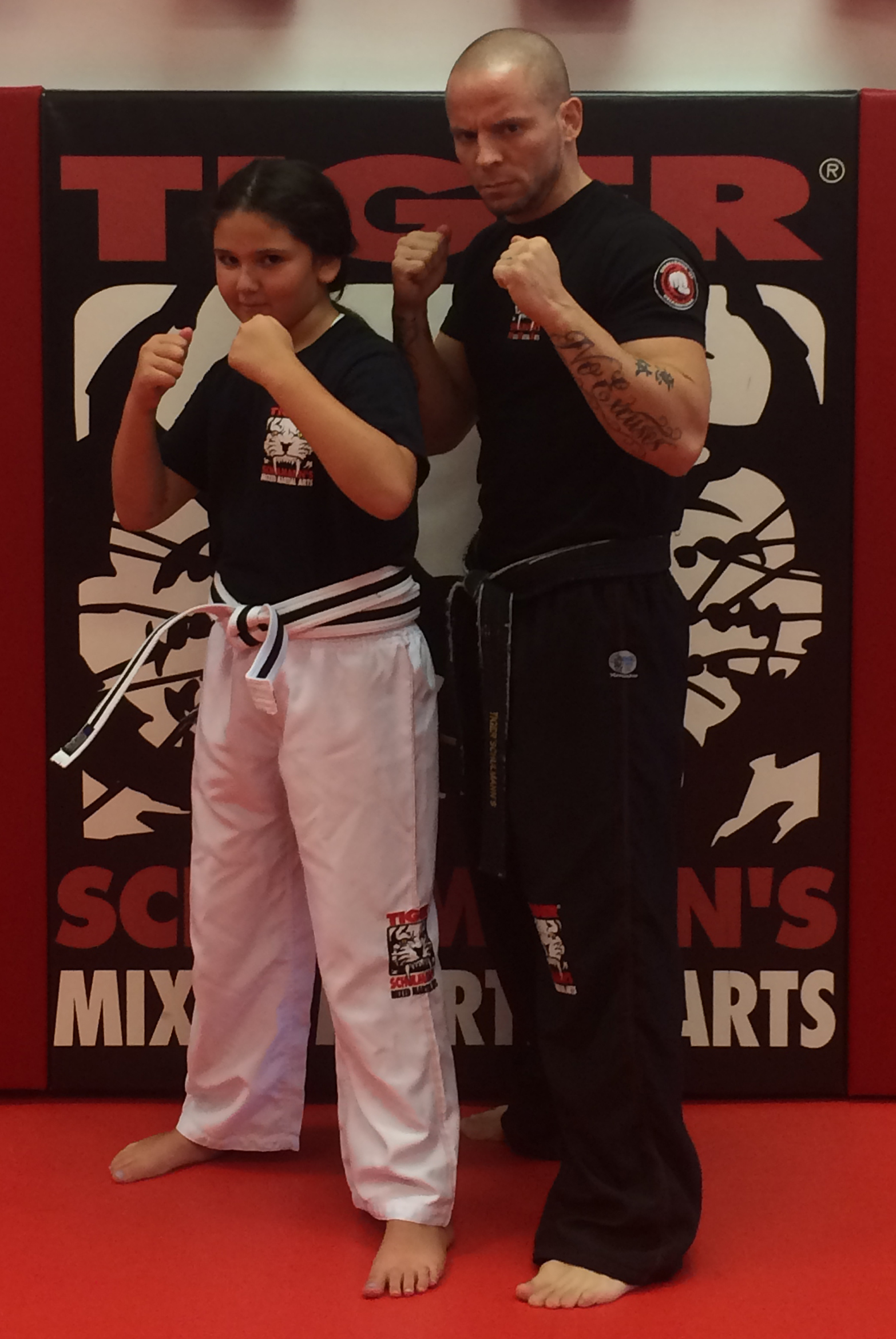 Tiger Schulmann's Martial Arts | Girl and Man Posing in Front of TSMA Logo